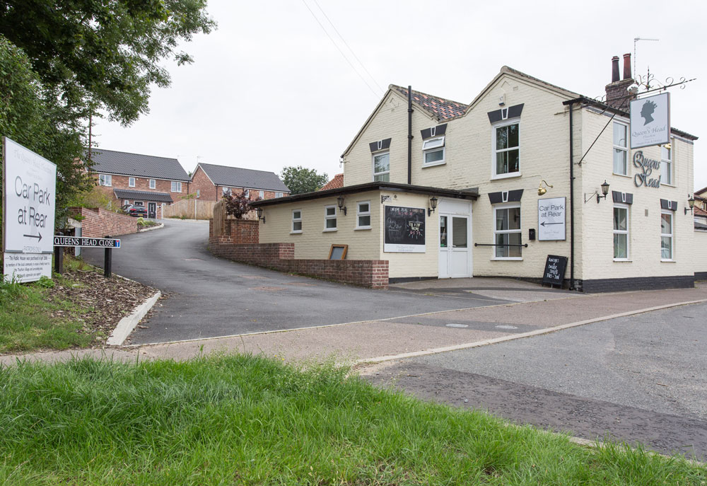Queens Head pub, Thurlton, Norfolk with new build development of 4 houses on land behind.